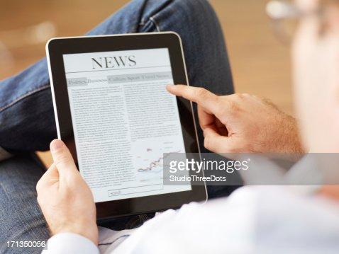 Mann Lesen der Zeitung auf tablet PC