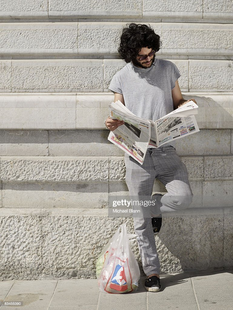man reading news paper in street : Stock Photo