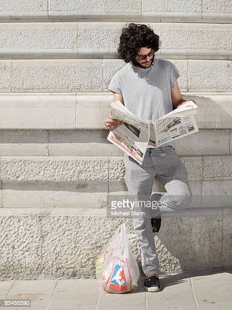man reading news paper in street