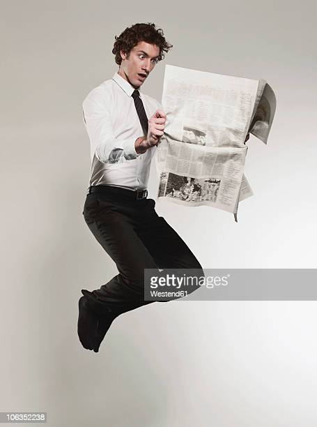 Man reading newspaper and jumping