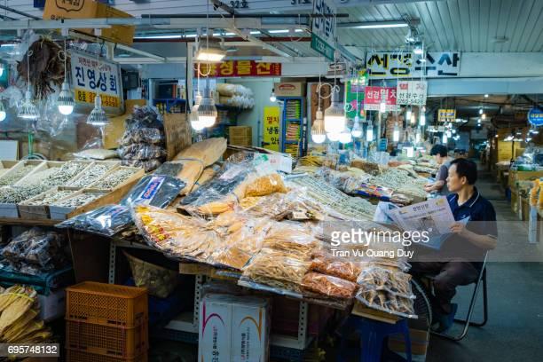 Man reading newspaper and selling dried foods at Gyeongdong Market, Seoul, Korea.
