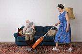 Man reading newspaper as woman vacuums