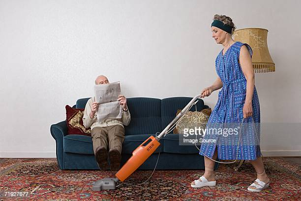 Man reading newspaper as woman vacuums
