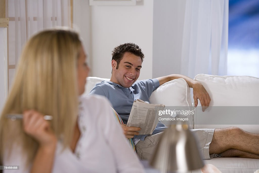 Man reading newspaper by woman : Stock Photo