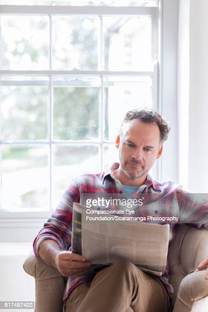 Man reading newspaper in arm chair