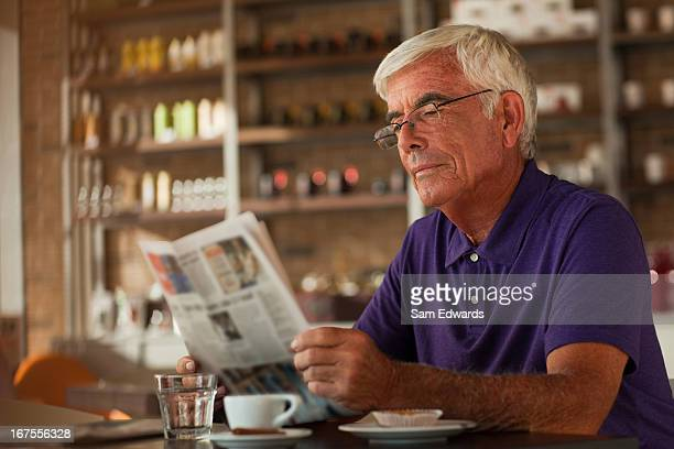 Homme lisant un journal dans le café