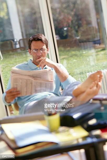 Man reading newspaper in home office (focus on face)