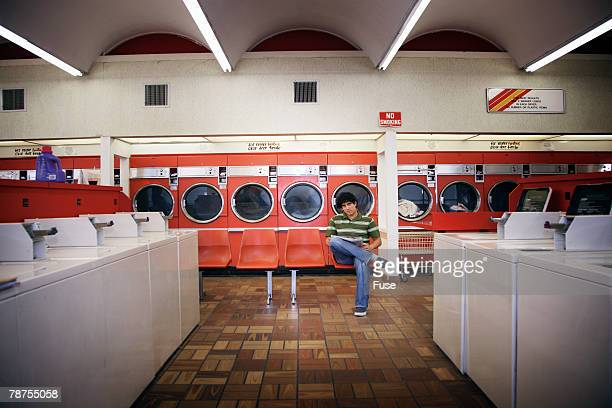Man Reading Newspaper in Laundromat