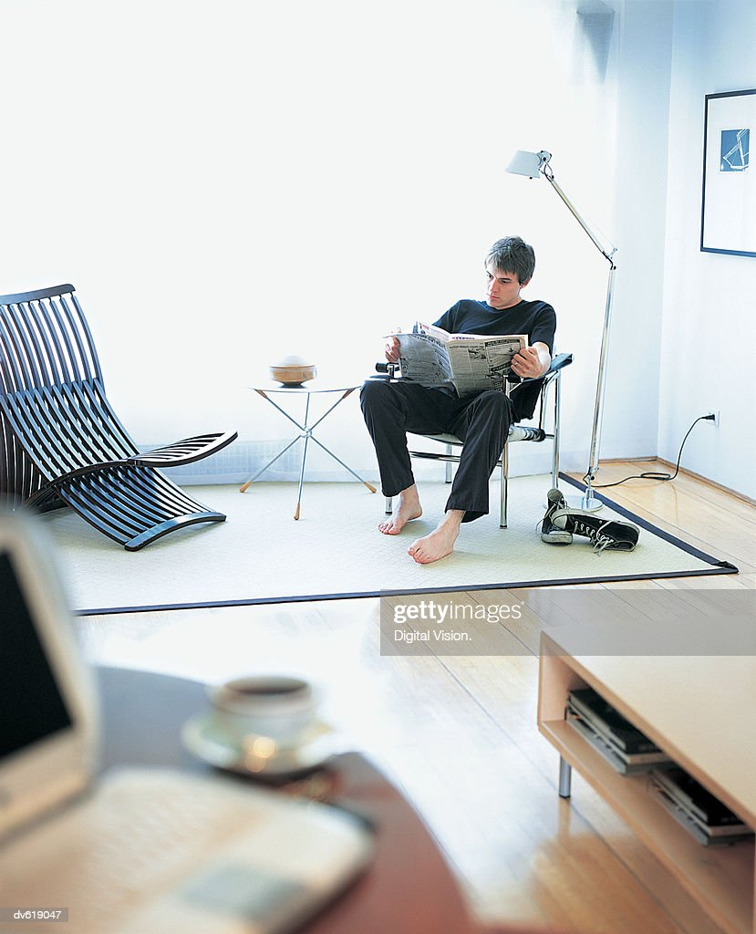 Man Reading Newspaper in Living Area : Stock Photo