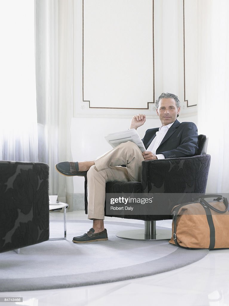Man reading newspaper in modern hotel suite  : Stock Photo