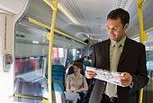 Man reading newspaper in train