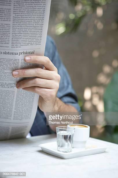 Homme lisant journal en plein air (concentrer sur les tasses de café