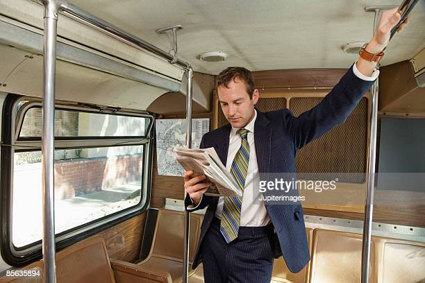 Man reading newspaper standing in bus