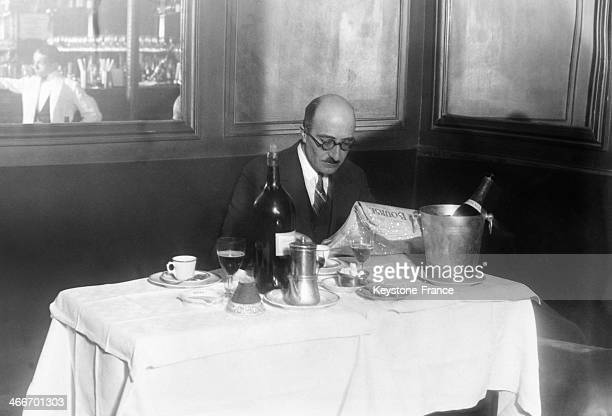 Man reading the Stock market prices during his lunch in a restaurant in May 1929 in Paris France