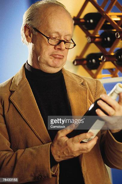 Man reading wine bottle label