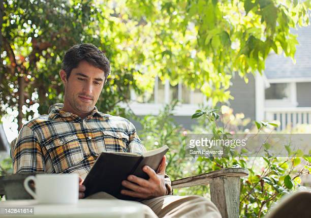 Man reading with cup of coffee outdoors