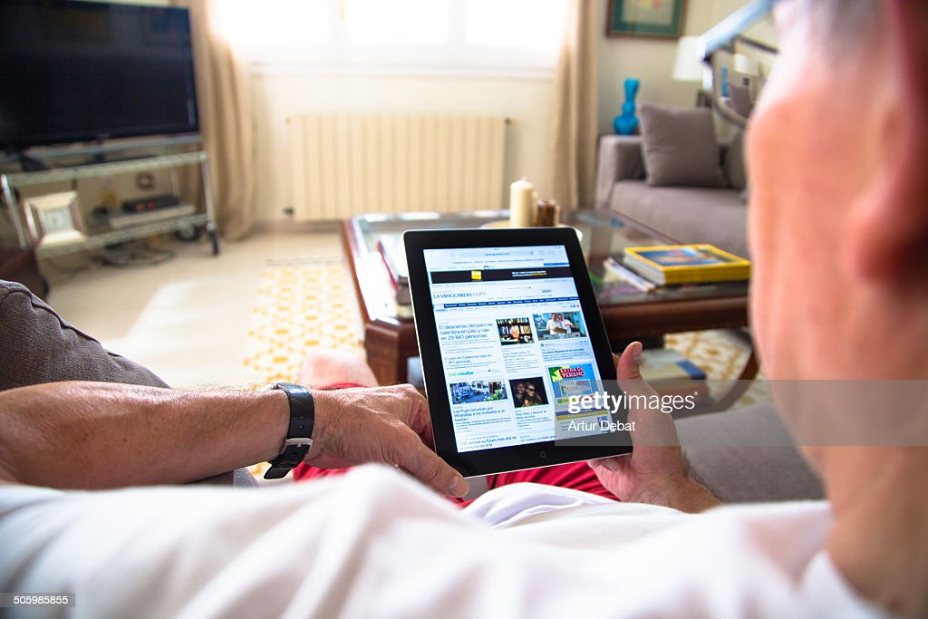 Man reading with reading glasses the news with iPad tablet sitting on living room home with warm light through the window at summer time.