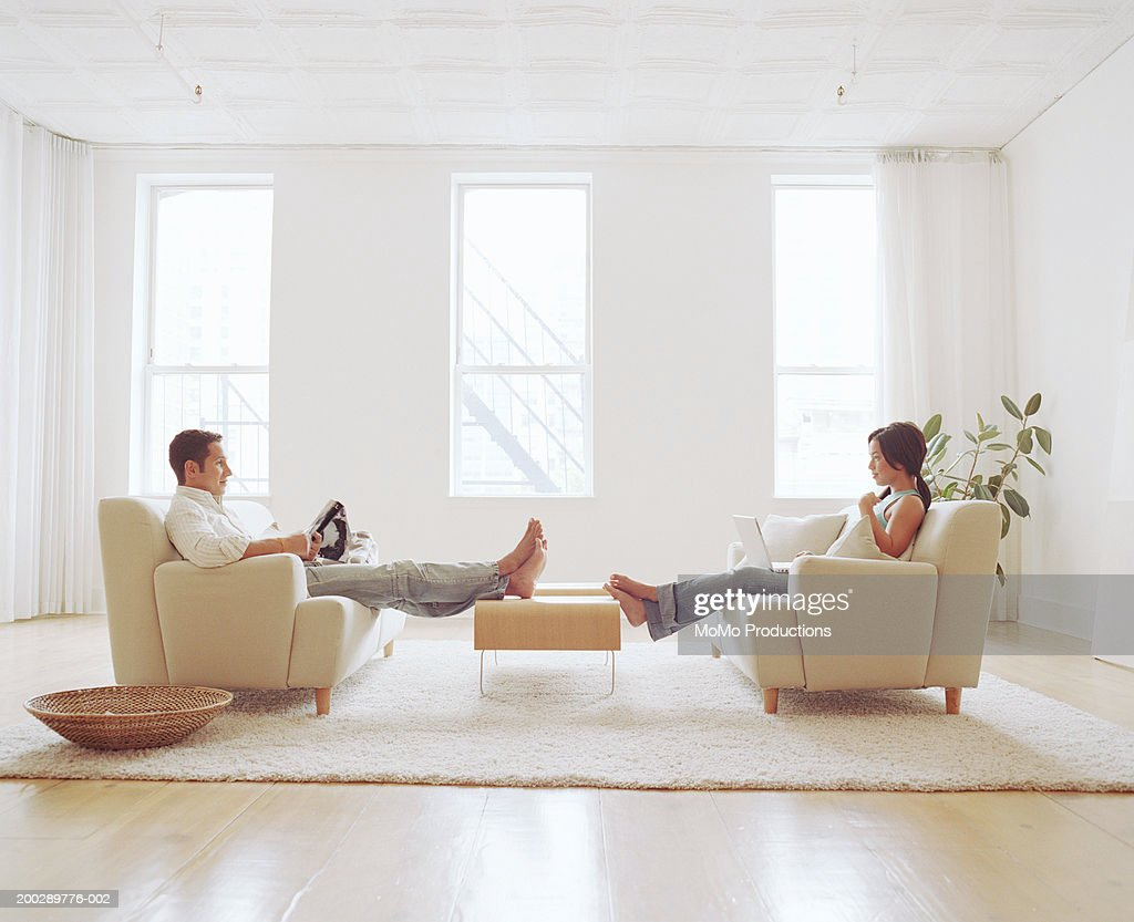 Man reading, young woman using laptop in living room, side view