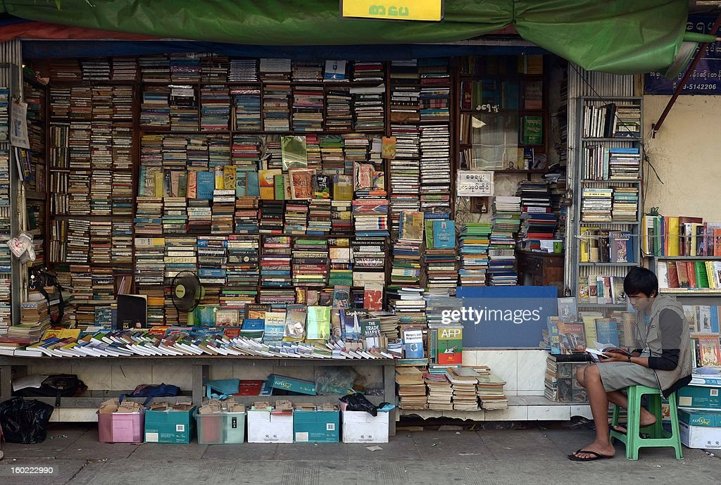 A man reads a book at a bookshop in downtown Yangon on January 28, 2013. Myanmar on January 28 announced a deal with international lenders to cancel nearly 6 billion USD of its debt, another milestone in the rapid transformation of the former junta-ruled nation. AFP PHOTO/Ye Aung THU