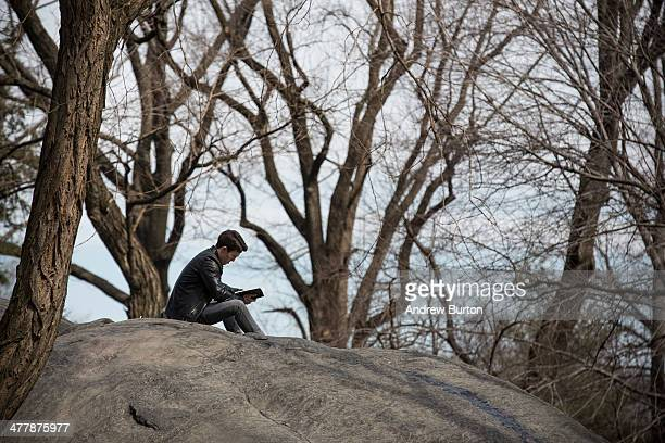 A man reads a book Central Park on March 11 2014 in New York City After an unusually frigid winter temperatures are supposed to reach into the 60s...