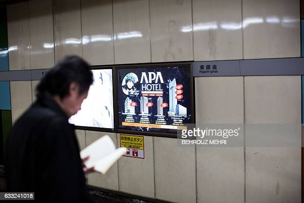 A man reads a book in front of an advertisement for the APA hotel group as he waits for a train at a subway station in Tokyo on February 1 2017...