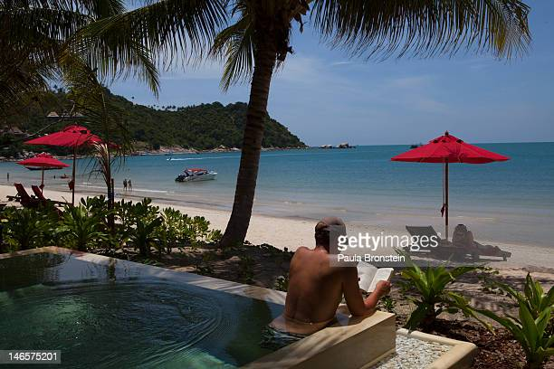 A man reads a book in his pool villa along the beach at the Anantara Rasananda resort June 18 2012 on the island of Koh Phangan off the coast of Koh...