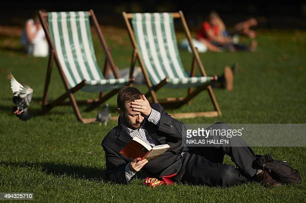 A man reads a book in the afternoon sunshine in a park in London on October 26 2015 AFP PHOTO / NIKLAS HALLE'N