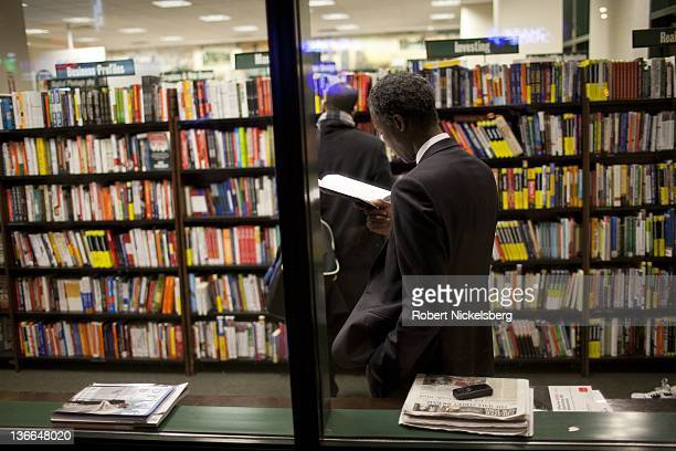 A man reads a book in the business section of a Barnes Noble Bookstore December 23 2011 in Brooklyn New York