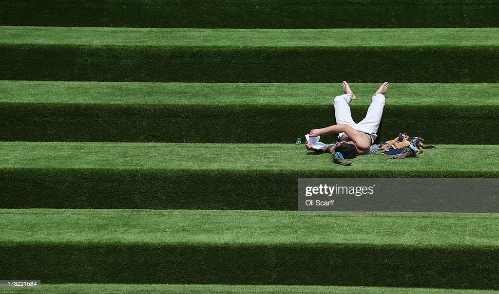 A man reads a book in the sunshine on steps covered in artificial grass on July 10, 2013 in London, England.