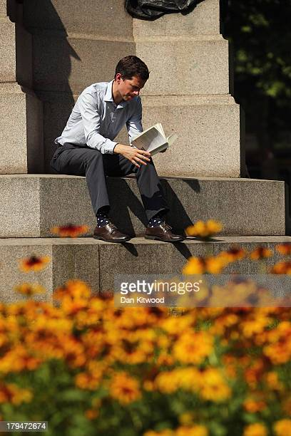 A man reads a book in Victoria Embankment Gardens on September 4 2013 in London England Much of Britain is experiencing higher than average...