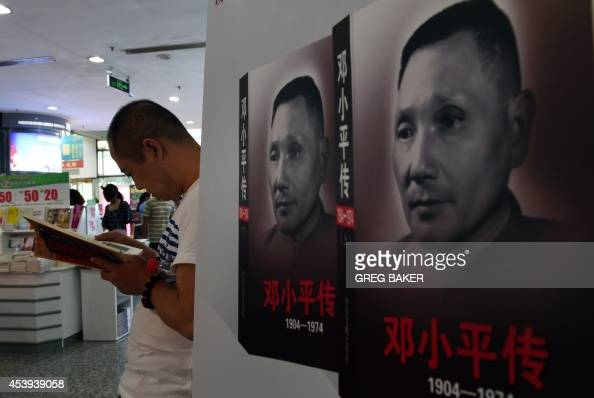 A man reads a book near posters for a newly issued biography about late Chinese leader Deng Xiaoping at a bookstore in Beijing on the 110th...