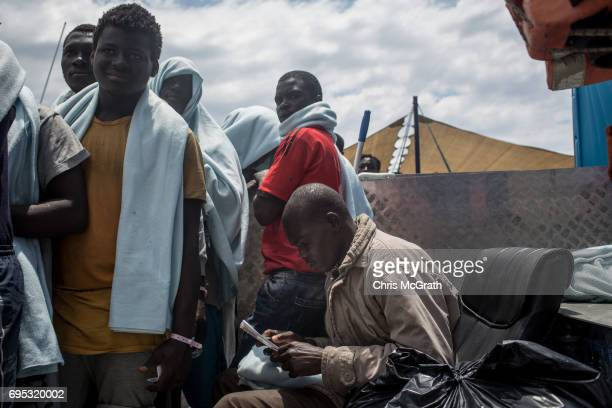 A man reads a brochure from the Italian authorities given out to refugees and migrants as they arrive in port onboard the Migrant Offshore Aid...
