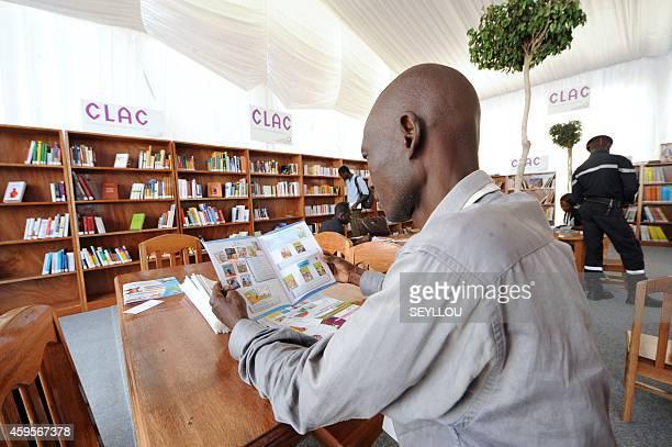 A man reads a brochure in the 'Village de la Francophonie' on November 25 2014 in Dakar ahead of the 15eme Sommet de la Francophonie The Organisation...