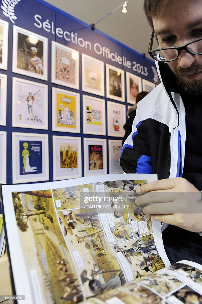 A man reads a comic book in front of the Official selection wall on the last day of the Comic book festival of Angouleme on February 3, 2013 in Agouleme, western France. The awards ceremony will take place today.