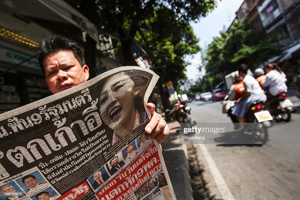 A man reads a copy of a newspaper featuring ousted Prime Minister Yingluck Shinawatra and interim Prime Minister Niwattumrong Boonsongpaisan on its front page in the Sathorn financial district in Bangkok, Thailand, on Thursday, May 8, 2014. The baht fell to a one-month low and stocks slumped on concern global investors will shun Thailand after a court ruling to remove Yingluck Shinawatra as prime minister worsened the nation's political crisis. Photographer: Dario Pignatelli/Bloomberg via Getty Images