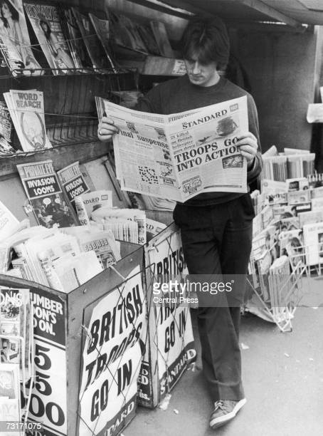 A man reads a copy of the Evening Standard at a London newsstand during the Falklands War 1982 The headlines read 'Troops Go Into Action' and...