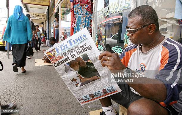 A man reads a daily newspaper reporting on its frontpage about the political situation after a deadline imposed by Fijian military commander Voreqe...