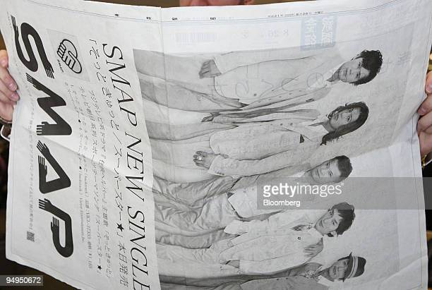 A man reads a fourpage newspaper ad with a picture of SMAP a Japanese pop group on the Aug 26 morning edition of the Sankei newspaper in Tokyo Japan...