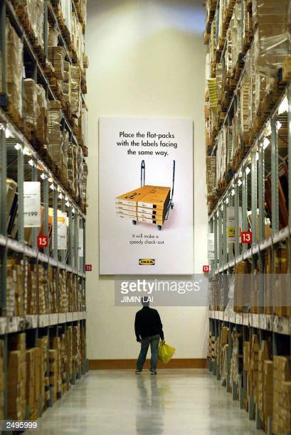 A man reads a huge poster inside the newest Swedish IKEA giant furniture store on its opening day in Kuala Lumpur 14 August 2003 IKEA's newest store...