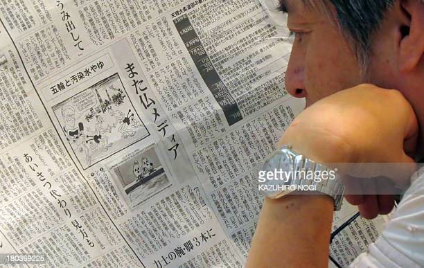 A man reads a Japanese local newspaper reporting on cartoons published in a French newspaper in Tokyo on September 12 2013 Japan voiced anger...