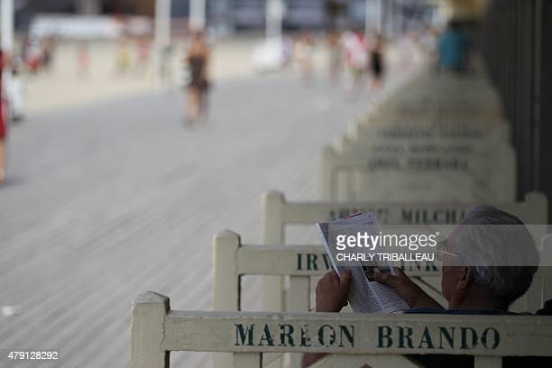 A man reads a magazine near the beach of the French northwestern city of Deauville on July 1 as a blistering heatwave sweeps through Europe with...