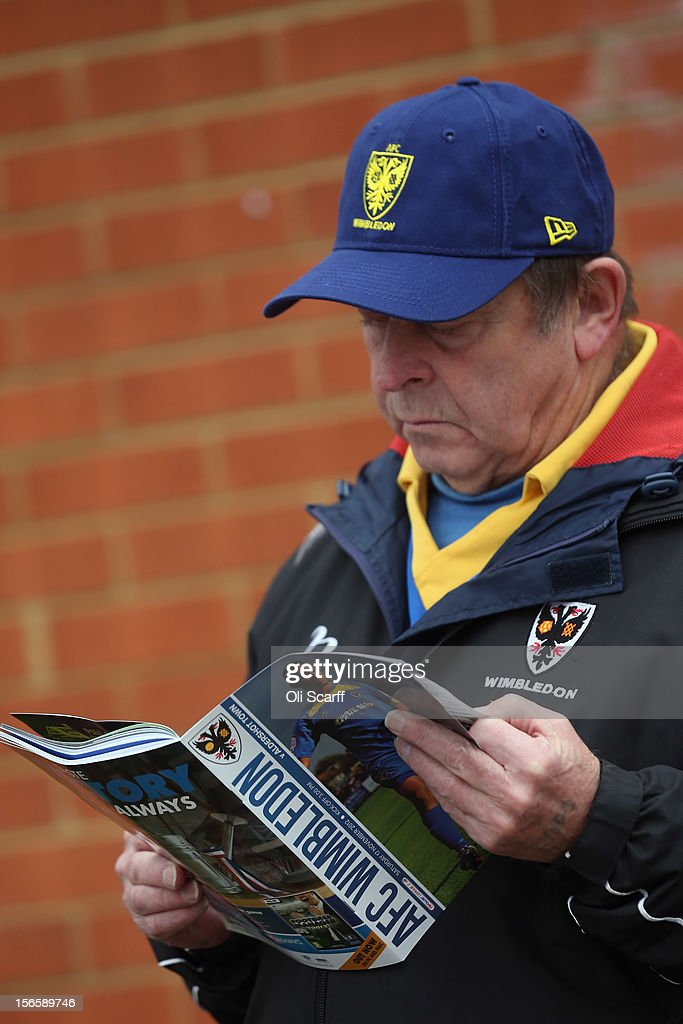 A man reads a match programme outside AFC Wimbledon's stadium before the npower League Two match between AFC Wimbledon and Aldershot Town at the Cherry Red Records Stadium on November 17, 2012 in Kingston upon Thames, England. on December 1, 2012 League Two AFC Wimbledon, the football club formed in 2002 by supporters unhappy with their club's relocation to Milton Keynes, will play an FA Cup tie against League One Milton Keynes Dons, which Wimbledon F.C. controversially became.