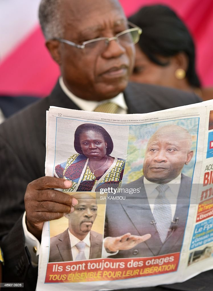 A man reads a news paper picturing Ivory Coast's former president and FPI member <a gi-track='captionPersonalityLinkClicked' href=/galleries/search?phrase=Laurent+Gbagbo&family=editorial&specificpeople=239000 ng-click='$event.stopPropagation()'>Laurent Gbagbo</a> (R), Leader of the 'Young Patriots' and Ivorian ex-president's right-hand man Charles Ble Goude (Down) and Ivory Coast's former president wife Simone Gbagdo (up) and reading in French 'They are still hostages. Together for their liberation' on April 11, 2015 in Abidjan during a commemoration of the anniversary of their arrest by the International Criminal Court of The Hague, on charges of crimes against humanity after post-election violence in 2011. AFP PHOTO/ SIA KAMBOU