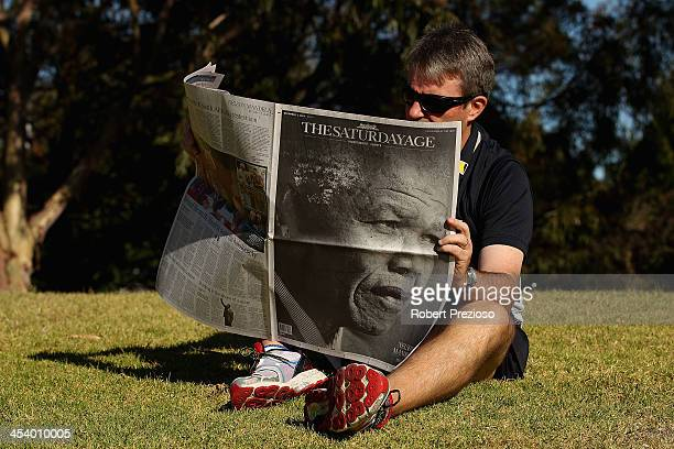 A man reads a newspaper after the death of Nelson Mandela on December 7 2013 in Melbourne Australia Mandela was a leader that helped conquer...