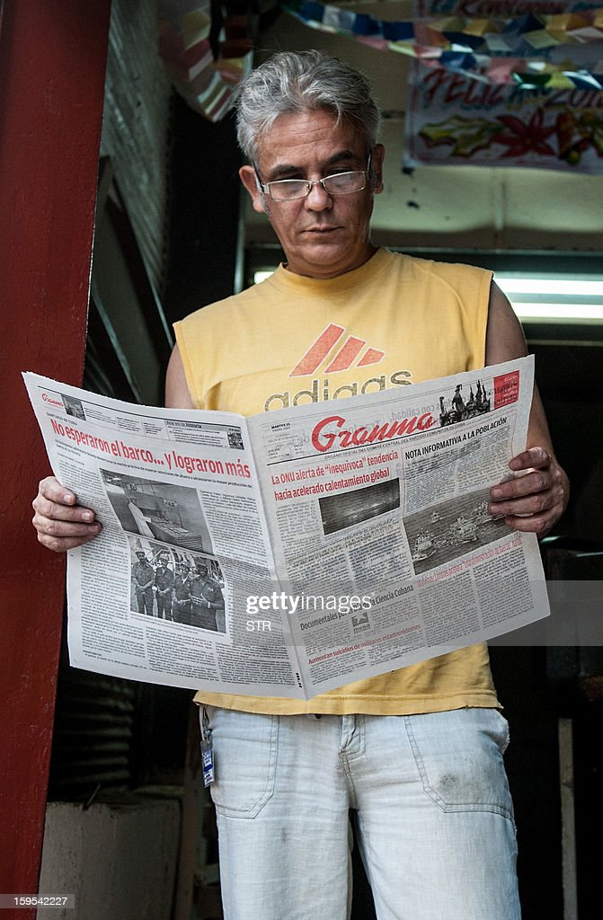 A man reads a newspaper announcing a cholera outbreak, in Cerro Municipality, on January 15, 2013 in Havana. The official newspaper Granma announced today a new cholera outbreak that has allegedly sickened 51 people in Havana.