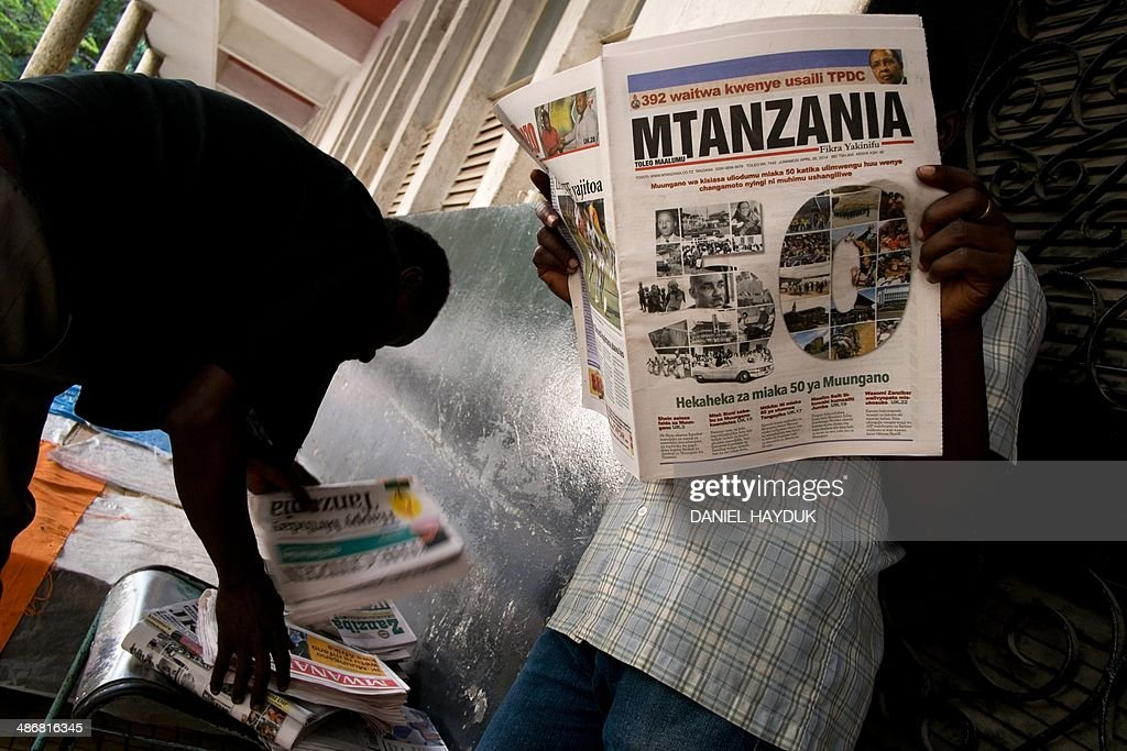 A man reads a newspaper announcing the 50th anniversary of the Union Day in Tanzania, which celebrates the union of Zanzibar and Tanganyikain, in Dar es Salaam on April 26, 2014. AFP PHOTO Daniel Hayduk