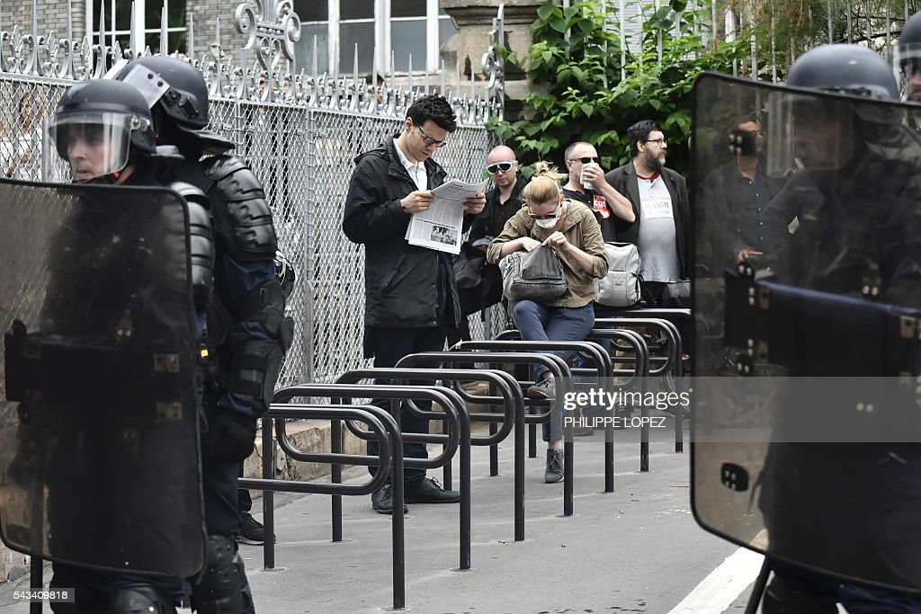 A man reads a newspaper as French anti-riot police stands guard during a demonstration against controversial labour reforms, on June 28, 2016 in Paris. Thousands of people took to the streets of Paris today in the latest protest march in a marathon campaign against the French Socialist government's job market reforms. / AFP / PHILIPPE