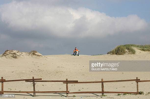 A man reads a newspaper as he takes sun bath on Romes nearest beach in Lido di Ostia 13 January 2007 Italy recorded its warmest December last month...