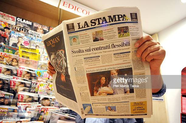 A man reads a newspaper at a newstand the front page of which features a photograph of Prince William Duke of Cambridge and Catherine Duchess of...