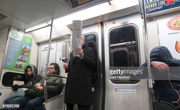 A man reads a newspaper between three other sleeping commuters on an early morning PATH train to New York City on November 15 in Hoboken New Jersey
